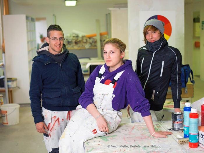 3 handwerkliche Auszubildende in einer Werkstatt